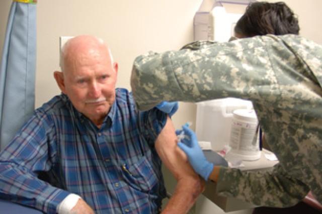 Army Public Health Nurse Capt. Lakeisha Jones administers the influenza vaccination to retiree Delbert Bryan during the 2010 Retiree Health Fair, Oct. 30.