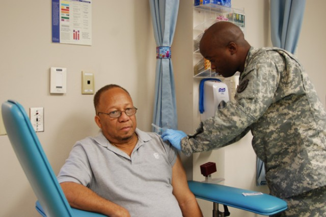 Staff Sgt. Ottis Jenkins, Internal Medicine NCOIC, administers the influenza vaccination to Army retiree Carlos Coppin during the 2010 Retiree Health Fair, Oct. 30.
