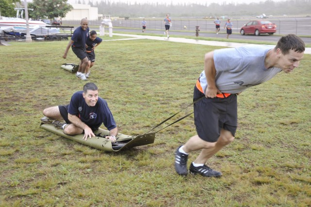 Soldiers of Headquarters Headquarters Company, 25th Combat Aviation Brigade, compete in a SKED litter-pull during HHC\'s 'Iron Eagle' battle focused physical fitness at Wheeler Army Airfield, Oct. 29.