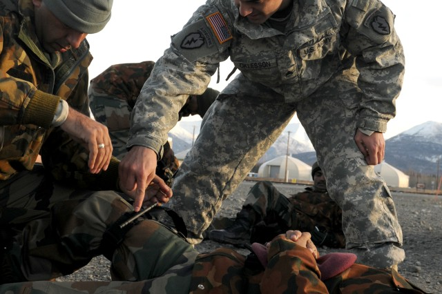 Sgt. Dakota Oklesson, senior line medic with Apache Troop, 1st Squadron (Airborne), 40th Cavalry Regiment, 4th Brigade Combat Team (Airborne), 25th Infantry Division, helps an Indian Army soldier apply a tourniquet during their first day of joint training for Yudh Abhyas 2010 Nov. 1 at the Battle Command Training Center and Education Center on Joint Base Elmendorf-Richardson, Alaska.