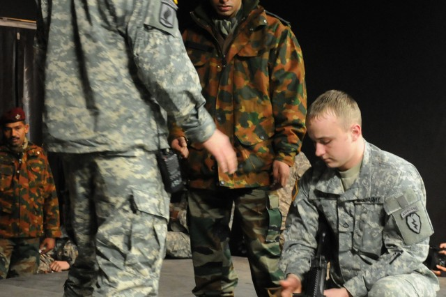 Sgt. Galan Carter, team leader with 1st Squadron (Airborne), 40th Cavalry Regiment, 4th Brigade Combat Team (Airborne), 25th Infantry Division, and Pfc. Joshua Good, gunner, 1-40th CAV, 4th ABCT, 25th ID, instruct Indian soldiers on loading the M-249 light machine gun during their first day of joint training for Yudh Abhyas 2010 Nov. 1 at the Battle Command Training Center and Education Center on Joint Base Elmendorf-Richardson, Alaska.