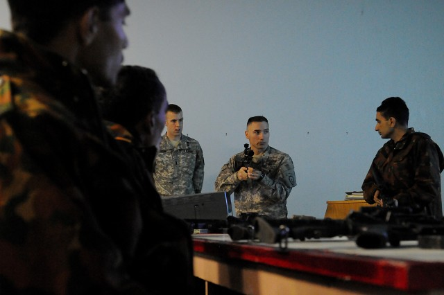 Sgt. David Lowry, section leader with Alpha Troop, 1st Squadron (Airborne), 40th Cavalry Regiment, 4th Brigade Combat Team (Airborne), 25th Infantry Division explains proper fire positioning of a M-4 carbine to Indian Army soldiers during their first day of joint training for Yudh Abhyas 2010 Nov. 1 at the Battle Command Training Center and Education Center on Joint Base Elmendorf-Richardson, Alaska.