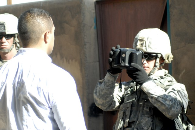 Sgt. Nike Ferzacca, 6th Squadron, 9th Cavalry Regiment, 3rd Brigade Combat Team, 1st Cavalry Division, uses the HIIDE to document the retinal scan and fingerprints of a role-playing Iraqi.