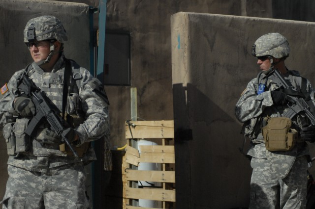 3rd Brigade Combat Team, 1st Cavalry Division Soldiers provide security for squad members serving a search warrant at the National Training Center, Fort Irwin, Calif., to search for material used in making homemade bombs. Units conduct the training prior to a two-week mission rehearsal exercise to prepare them for their upcoming deployment to Iraq.