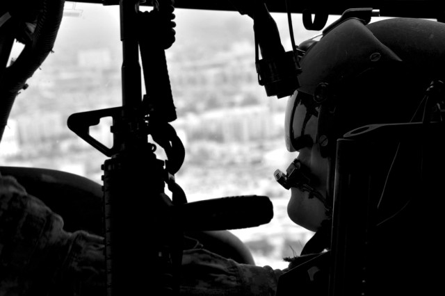 A U.S. Army Black Hawk pilot turns his head to check his aircraft's gauges while flying over Baghdad this summer. The pilot belongs to the Enhanced Combat Aviation Brigade, 1st Inf. Div., the last aviation brigade to deploy as part of Operation Iraqi Freedom and the only aviation brigade supporting Operation New Dawn.