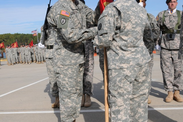 Brig. Gen. Robin Akin, (right), the 3rd Sustainment Command (Expeditionary) commanding general, passes the 7th Sustainment Brigade colors to Col. Lawrence Kominiak, the incoming brigade commander, during a change of command and responsibility ceremony at 3rd Port Tuesday.