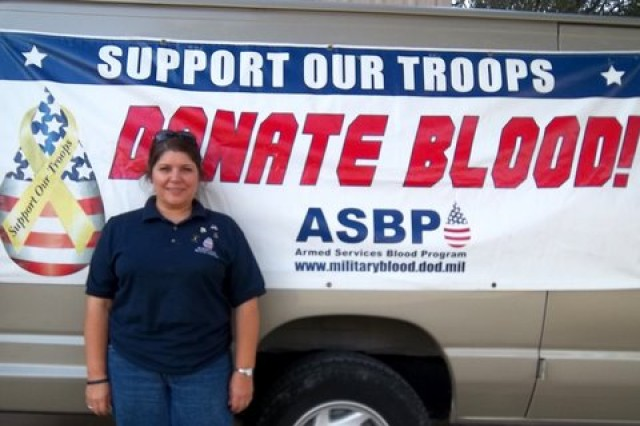 Donna Smith, a volunteer blood drive coordinator, poses with the van from Fort Hood at the McGregor ROTC blood drive