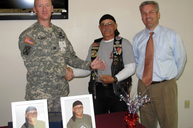 Capt. Steven McDaniel presents Ron Decker with a plaque for his entry into the Blood Donation Hall of Fame while Dave Toschik assists.  Robertson Blood Center at Fort Hood on October 20, 2010.