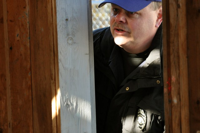 Patrol Officer Scott Woodward steps through a doorway Nov. 1 at a Hudson, Mass., training area while teaching maneuver techniques to USAG Natick police officers and security guards.