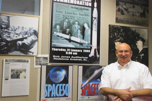 Aviation and Missile Command historian Mike Baker stands in his office among posters that recall the history of Redstone Arsenal's role in the early years of space exploration. Known as 'Mr. Redstone,' Baker continues to tell the story of the German and American rocket scientists whose contributions during those early years still influence the science and technology used by today's missile and space programs.