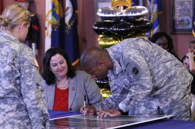 FORT BLISS, Texas -- Katherine Hammack (center), the assistant secretary of the Army for installations, energy and environment, smiles as Fort Bliss Commanding General Maj. Gen. Dana J. H. Pittard signs his name alongside hers Nov. 4 during Fort Bliss\' Army Family Covenant at the 1st Armored Division Museum. Hammack spent the day touring the growing post and meeting its leaders, Soldiers, families and civilians.