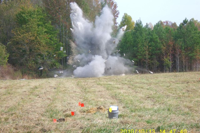 Two 81-mm World War II mortar rounds found in Rougemont, N.C., Oct 13, 2010, are detonated. The photo was taken from a safe distance of about 400 feet. The white objects flying through the air are some of the 75 sandbags, weighing up to 25 pounds each, used to contain fragmentation of the mortars during the explosion. The flags in the foreground mark where the shells were found.