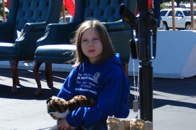 A child who came to the ceremony to remember Staff Sgt. Amy Krueger sits by the ceremonial boots and rifle displayed to honor the 13 Soldiers and civilians killed during the Fort Hood shooting incident Nov. 5, 2009.
