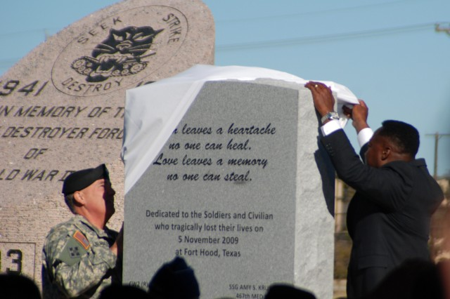Maj. Gen. William Grimsley, Fort HoodAca,!a,,cs senior commander, and Ron Taylor, Central Texas State president of the Association of the United States Army, unveil a new monument that rests in Memorial Park behind the III Corps headquarters on Fort Hood.
