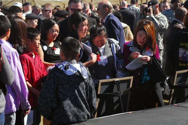Friends and family members of Pfc. Kham S. Xiong, who was killed Nov. 5, 2009, at Fort Hood's Soldier Readiness Processing Center, gather around his photo following a Remembrance Ceremony held at Fort Hood, Texas, Friday. The ceremony honored all 13 Soldiers killed last year.