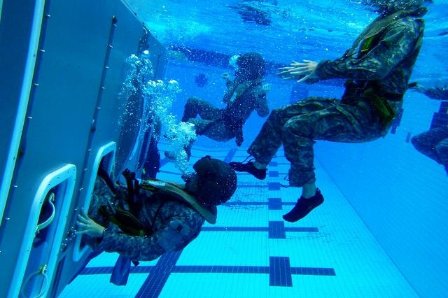 Pilots assigned to 2nd Squadron, 6th Cavalry Regiment, 25th Combat Aviation Brigade, free themselves from an overturned, submerged helicopter mock-up during the unit's Dunker Heeds training at Marine Corps Base Kaneohe Bay, Nov. 3.(Photo by Staff Sgt. Mike Alberts  25th Combat Aviation Brigade Public Affairs)
