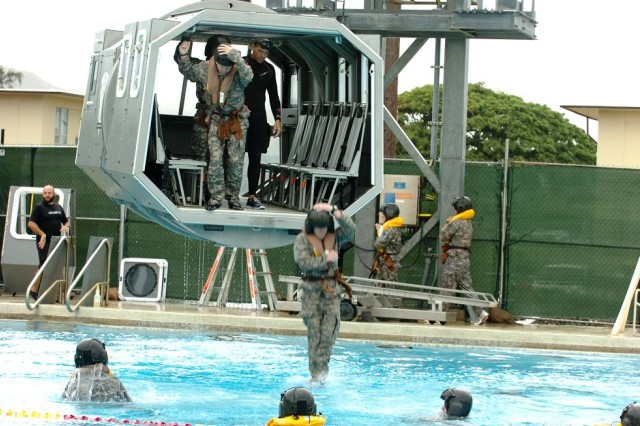 Pilots assigned to 2nd Squadron, 6th Cavalry Regiment, 25th Combat Aviation Brigade, leap from a suspended helicopter mock-up during the unit's Dunker Heeds training at Marine Corps Base Kaneohe Bay, Nov. 3.(Photo by Staff Sgt. Mike Alberts  25th Combat Aviation Brigade Public Affairs)