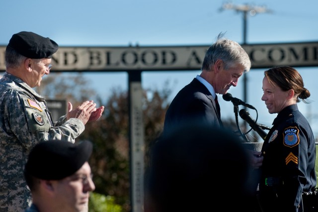 John McHugh, Secretary of the Army, awards Police Sgt. Kimberly Munley a medal while Chief of Staff of the U.S. Army, Gen. George W. Casey Jr., applauds the presentation during a Remembrance Ceremony in Fort Hood, Texas, Nov. 5, 2010. Fifty-two Soldiers and civilians were honored for their efforts to aid the wounded in the wake of the Nov. 5, 2009, shooting at Fort Hood.