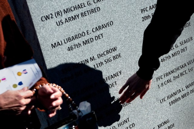 Unidentified family members and friends visit a memorial stone after it was unveiled during a ceremony commemorating the one-year anniversary of  the shootings on Fort Hood, Texas, Nov. 5, 2010.  Thirteen people were killed and dozens wounded, Nov. 5, 2009.