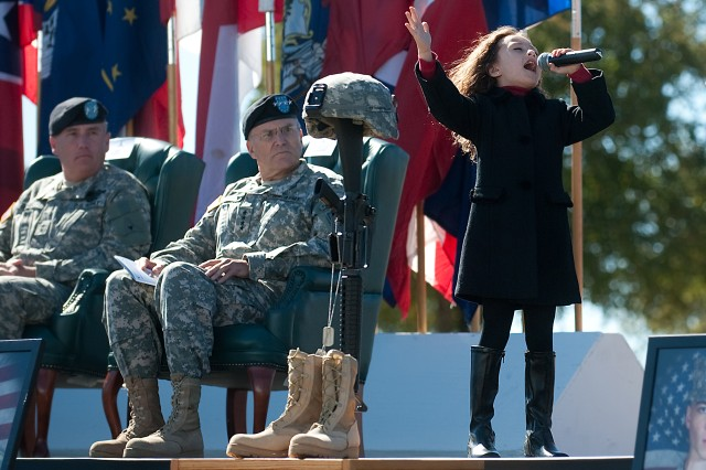 """Rhema Marvanne, 7, sings """"The Prayer"""" during a Remembrance Ceremony at Fort Hood, Texas, Nov. 5, 2010. The ceremony commemorated the lives of 13 people who died in a tragic shooting incident on the installation Nov. 5, 2009."""