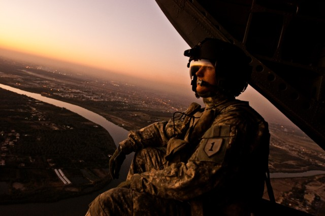 Spc. David Kovach, a Chinook crew chief serving in Iraq with the Enhanced Combat Aviation Brigade, 1st Infantry Division, sits on the tail ramp of his aircraft during a mission in the Baghdad area, Nov. 5. Kovach and other crew chiefs in the brigade have been flying nonstop during operations Iraqi Freedom and New Dawn, moving nearly 90,000 personnel, 4 million pounds of cargo, and flying over 15,000 flight hours since this March. (U.S. Army photo by Spc. Roland Hale, eCAB, 1st Inf. Div. PAO)