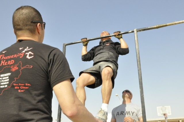 Cpl. Jonathan Rivera, from Headquarters and Headquarters Company, 20th Engineer Battalion, and a native of Mayaguez, Puerto Rico, performs chin-ups under the watch of Sgt. Fernando Perez, also of HHC, 20th Eng. Bn., and a Chicago native, during a Cross-Fit competition at Kandahar Airfield, Afghanistan, Nov. 5. Perez's T-shirt bears the names of the three Soldiers from the 510th Engineer Company killed in the Fort Hood shooting Nov. 5, 2009.