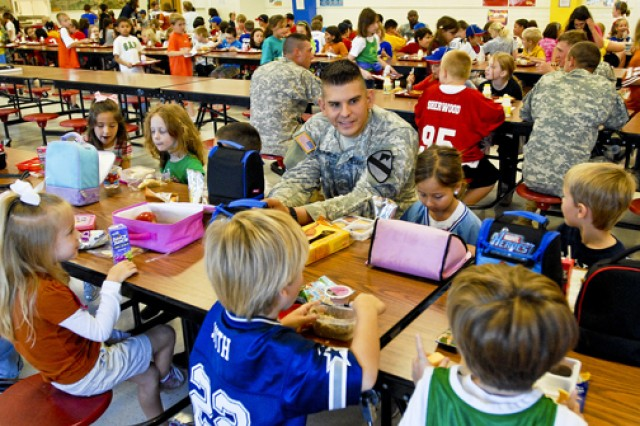 San Antonio, Texas native, 2nd Lt. Ronald Youngblood, a fire support officer with 2nd Battalion, 5th Cavalry Regiment, 1st Brigade Combat Team, 1st Cavalry Division, eats his lunch with students of Leon Heights Elementary Schools.  Students at local schools like Leon Heights Elementary near Army posts will benefit from Department of Defense Education Activity grants.