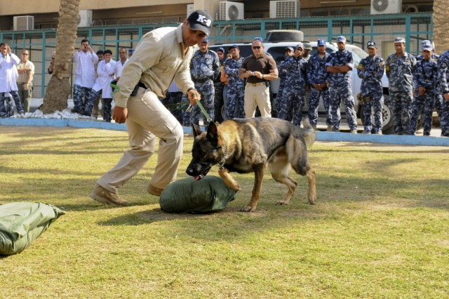 Newly-certified Iraqi Police Explosive-Detection Dog Handlers and their canines demonstrate their skills before marching in the Iraqi Police Canine Program ceremony at the Baghdad Police College Nov. 7.