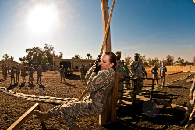 Pfc. Jennell Waelty, a Soldier serving on Camp Taji, Iraq, with the Enhanced Combat Aviation Brigade, 1st Infantry Division, swings across an obstacle, Nov. 7, during Demon Fury, a competition designed to test the full spectrum of Soldiers' combat skills.