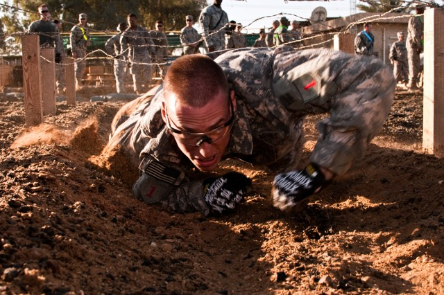 Sgt. Derek Czerniak, a Soldier serving on Camp Taji, Iraq, with the Enhanced Combat Aviation Brigade, 1st Infantry Division, crawls under a barbed wire obstacle, Nov. 7, during Demon Fury, a competition designed to test the full spectrum of Soldiers' combat skills.