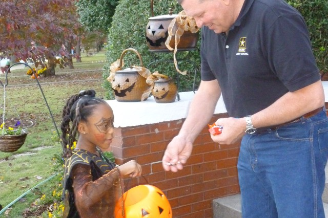 Gen. James D. Thurman, commanding general, U.S. Army Forces Command, gives some candy to trick-or-treater Lauren Maxam, 8, daughter of Sybil and Lt. Col. Ronald Rogers, G-5 planning officer, Third Army.