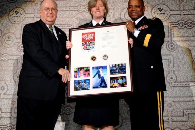 Army Under Secretary Dr. Joseph W. Westphal (left) and FMWRC Commander Maj. Gen. Reuben D. Jones presents an award to Lt. Col. Sharon McBride, a representative of Comprehensive Soldier Fitness, one of the sponsors of the 2010 Soldier Show. (cleared for public release, not for commercial use, attribution requested.)