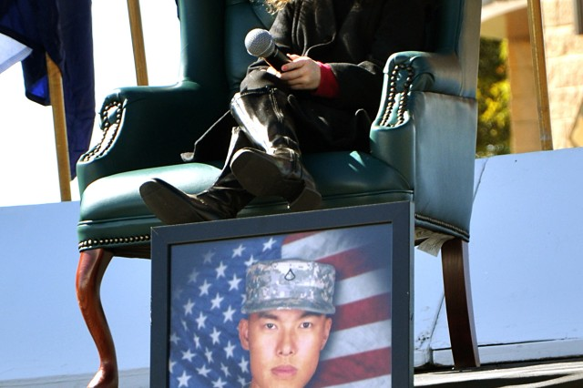 "FORT HOOD, Texas-Rhema Marvanne, of Carrollton, Texas, sits above the picture of Pfc. Kham Xiong, a Soldier who lost his life in the Nov. 5, 2009 shootings on Fort Hood. Rhema sang the song ""The Prayer,"" at the Remembrance Memorial Ceremony outside of the Division West Headquarters, Nov. 5."