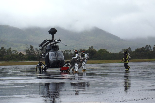 A Fire rescue team extracts a pilot, assigned to 2nd Squadron, 6th Cavalry Regiment, 25th Combat Aviation Brigade, from an OH-58D Kiowa Warrior helicopter during a simulated training event testing disaster readiness on Wheeler Army Airfield, Oct. 26.