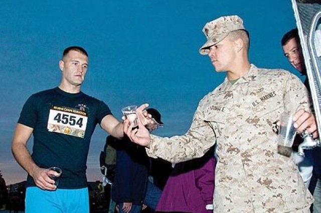Lance Cpl. Shawn Dingle, H&S Bn., HQMC, Henderson Hall, hands marathon runner, Matthew Lindauer from Columbus, Ohio, a cup of water at The 35th Marine Corps Marathon.