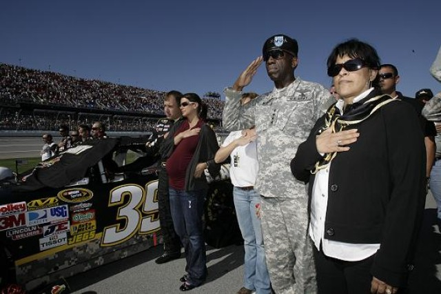 General William E. Ward, Commander, U.S. Africa Command, and his wife Joyce, (right) join the driver of the #39 U.S. Army Chevrolet, Ryan Newman, and his wife Krissie during the National Anthem prior to the start of the NASCAR AMP Energy Juice 500 Sprint Cup race October 31, 2010 at the Talladega Motor Speedway.