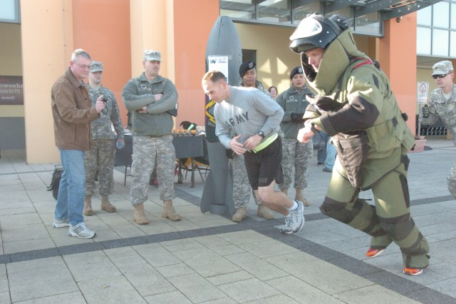 The 18th Combat Sustainment Support Battalion commander, Lt. Col. Reed Hudgins (left), starts the official run timer as Staff Sgt. Eric Johnson, a team leader with the 702nd Explosive Ordnance Disposal Company, starts his run to break the world record for a one-mile bomb suit run Oct. 30.