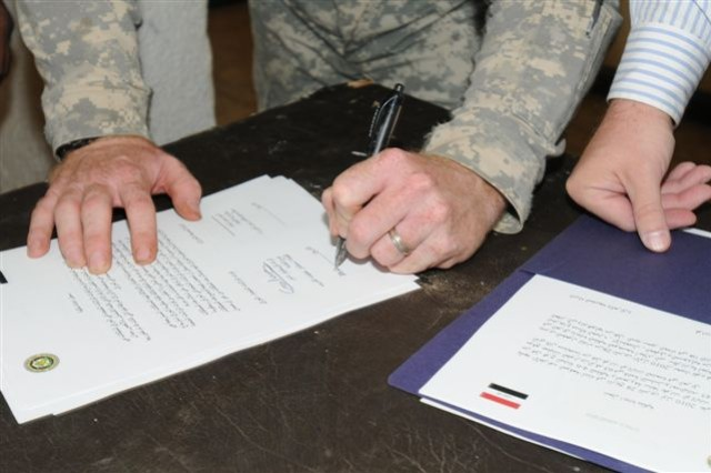 Maj. Christopher Adams, a Dayton, Ohio, native serving as an advisor to the 2nd Commandos and Department of Border Enforcement, signs documents transferring Joint Security Station Al Tib from the U.S. to the Government of Iraq.