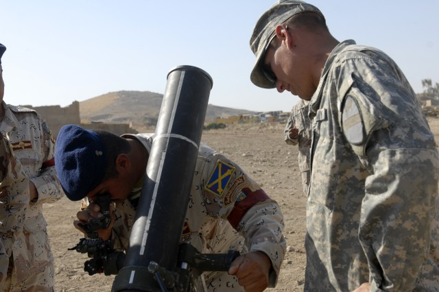CONTINGENCY OPERATING SITE MAREZ, Iraq-Spc. Scott David, a gunner assigned to the 1st Squadron, 9th Cavalry Regiment, 4th Advise and Assist Brigade, 1st Cavalry Division, assists an Iraqi Army Soldier assigned to the 6th Brigade, 3rd Division, while making adjustments to the 120mm mortar system Nov. 8.