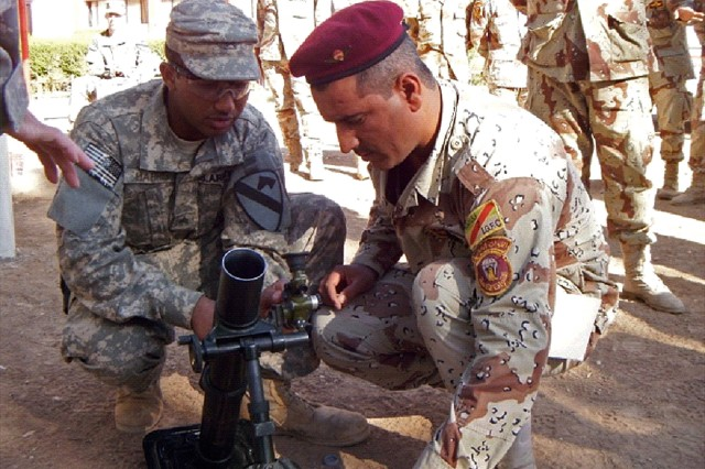 CONTINGENCY OPERATING SITE MAREZ, Iraq-Sgt. Andrew Harris (left), a squad leader from the mortar platoon of the 2nd Battalion, 7th Cavalry Regiment, 4th Advise and Assist Brigade, 1st Cavalry Division, teaches a 60-mm mortar familiarization class to Soldiers of the Iraqi Army's 2nd Division.