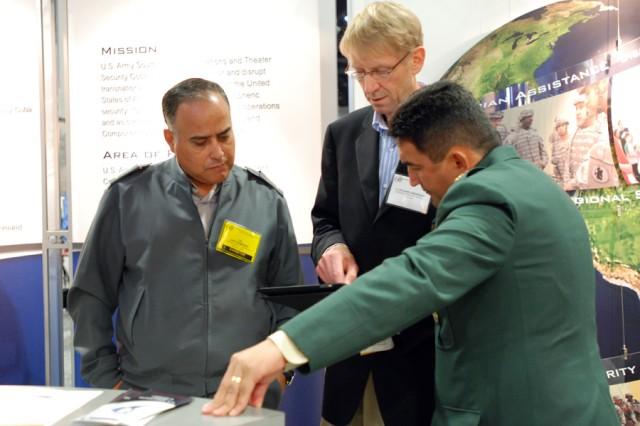 U.S. Army South foreign liaison officers Chilean Army Col. Luis Chamorro (left) and Colombian Army Col. German Lopez (right) speak to a visitor at the Army South booth during the 2010 Association of the United States Army Annual Meeting and Exposition at the Walter E. Washington Convention Center in Washington, D.C., Oct. 24.