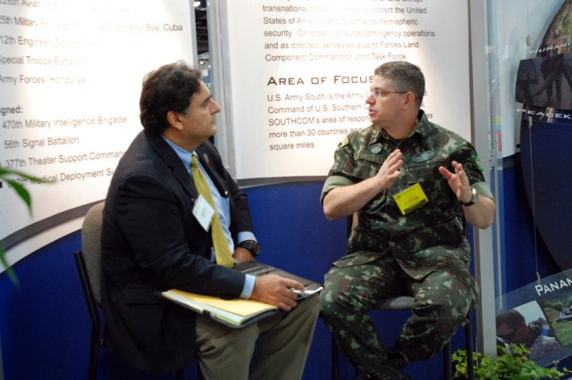 Brazilian Col. Valerio Luiz Lange (right), a U.S. Army South foreign liaison officer, speaks to a visitor at the Army South booth during the 2010 Association of the United States Army Annual Meeting and Exposition at the Walter E. Washington Convention Center in Washington, D.C., Oct. 25.
