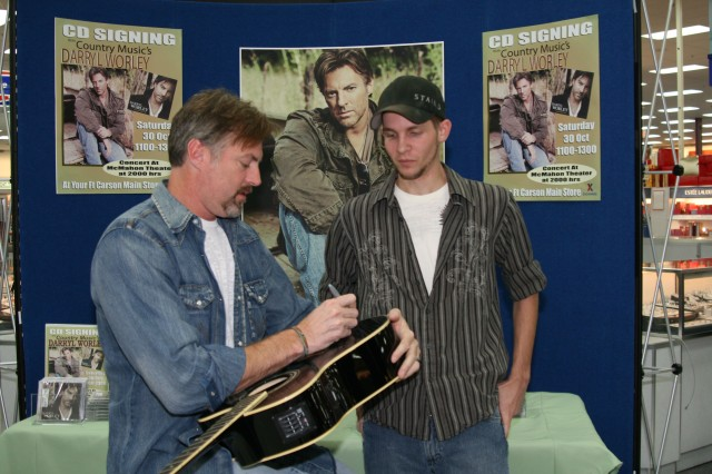"James Daffron gets his guitar signed bycountry music singer Darryl Worley Oct. 30 at the post exchange at Fort Carson, Colo. Worley visited Fort Carson as a stop on his ""God & Country"" tour and performed a free concert."
