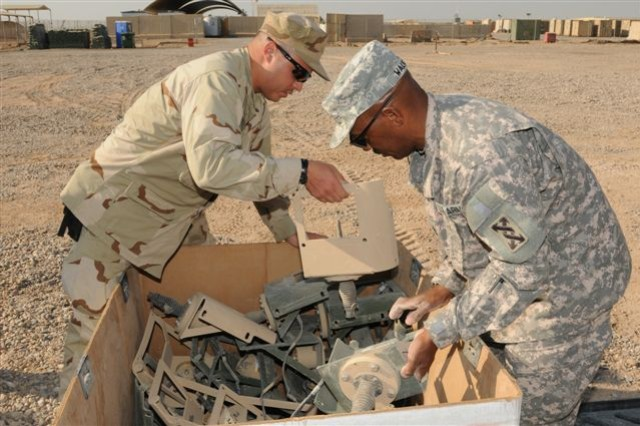 Sgt. 1st Class Larry Walker, a native of Palm Harbor, Fla., and the noncommissioned officer-in-charge of the mobile redistribution teams for Operation Clean Sweep with 319th Transportaion Company, inspects excess supplies with Chief Petty Officer David Rabon, a New York native serving with Riverine Squadron 1, in Basra Nov. 4.