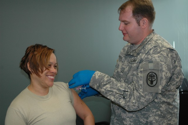 (FORT BRAGG, N.C., Nov. 9, 2010) Master Sgt. Peggy Melendez, USARC G-4, appears happy to be inoculated against the seasonal and H1N1 flu by Pfc. Jon Muesing, a medic with the Womack Family Medicine Residency Clinic here.