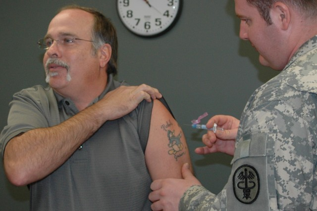 (FORT BRAGG, N.C., Nov. 9, 2010) Scott Monk of the FORSCOM Adjutant General office braces himself for his combined seasonal and H1N1 flu inoculation administered by Pfc. Jon Muesing, a medic with the Womack Family Medicine Residency Clinic here.