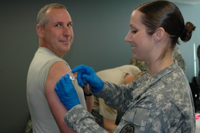 (FORT BRAGG, N.C., Nov. 9, 2010) Staff Sgt. Angela Bowley, a medic with the Womack Family Medicine Residency Clinic, enjoys her work as she gets ready to stick it to Master Sgt. Chaunsey Fowler of the FORSCOM G-1.  She vaccinated him against the seasonal and H1N1 influenza viruses at the U.S. Army Forces Command (FORSCOM) and U.S. Army Reserve Command (USARC) Forward offices here.