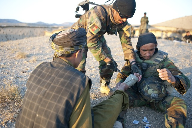 Afghan Soldier medics with 3rd Commando Kandak perform first aid on an Afghan's injured foot, Nov. 7, 2010, in Arghistan District, Kandahar Province, Afghanistan. The Commandos, advised by Soldiers with Special Operations Task Force - South, are conducting operations to rid insurgents from the region. The injury was preexisting and not related to the operation. (U.S. Army photo by Spc. Daniel P. Shook/Special Operations Task Force - South).