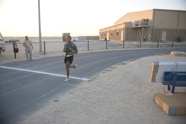 CAMP ARIFJAN, Kuwait - Capt. Daniel Brown, a native of Tampa, Fl., who serves as the battle captain with the 53rd Infantry Brigade, crosses the finish line first during the Third Army 5K Birthday Run at Camp Arifjan, Kuwait, Nov. 7. Third Army celebrated its 92 years of history, ranging from its mission in the trenches of Germany during World War II to their current mission of balancing a complex logistical mission in order to support the Warfighters in Iraq and Afghanistan from Kuwait, by participating in a 5-km. run.    (U.S. Army photo by Sgt. Ryan Hohman)