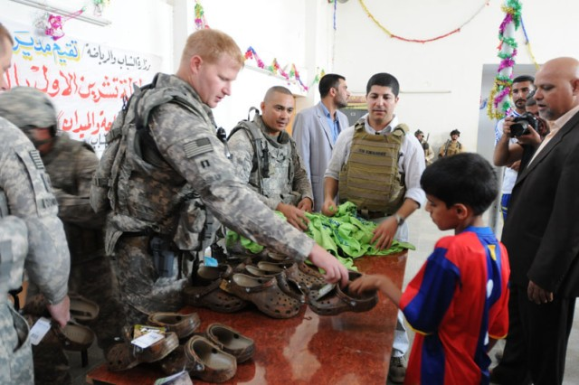 Capt. James Reilly of Troop A, 1st Squadron, 3rd Armored Cavalry Regiment passes out shoes to children after the re-opening of the Husayniyah Youth Center.